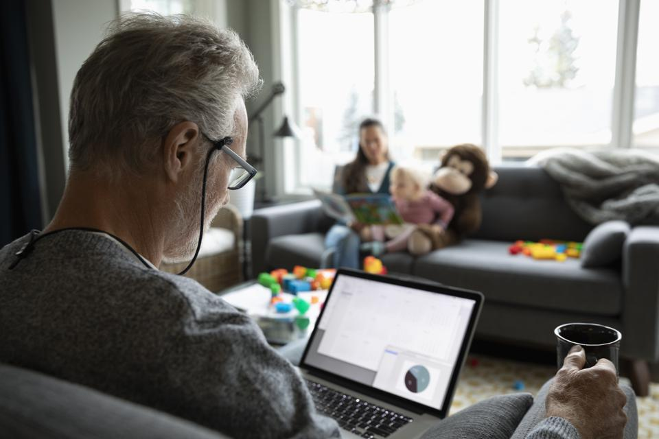 Senior man using laptop and drinking coffee in living room