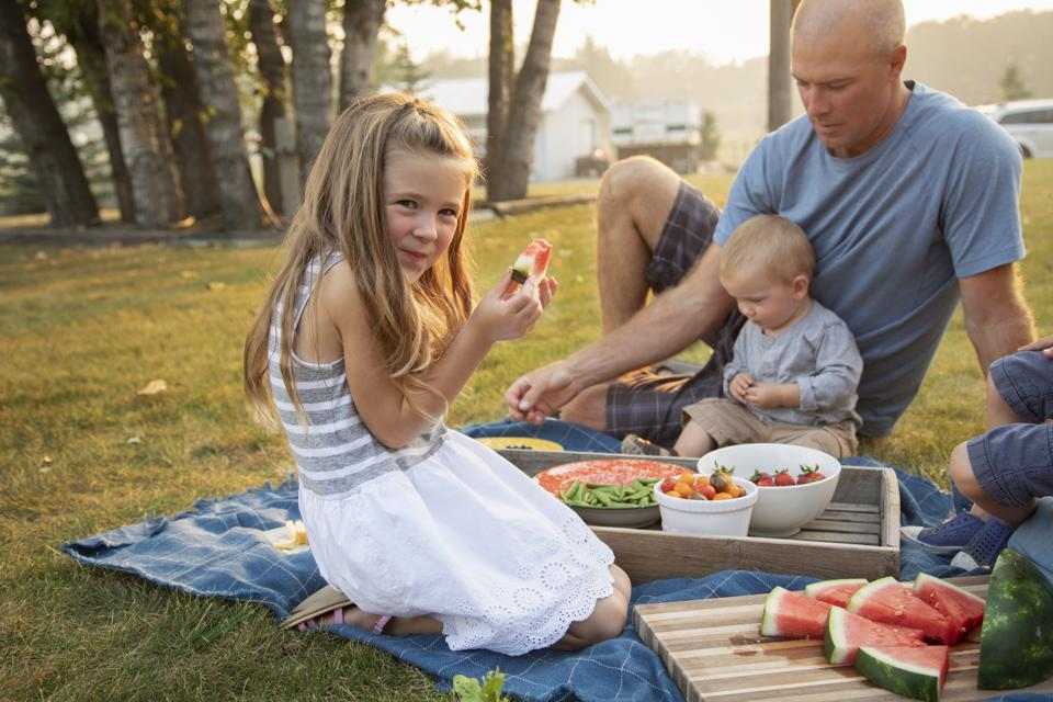 Portrait happy girl eating watermelon, enjoying picnic with family