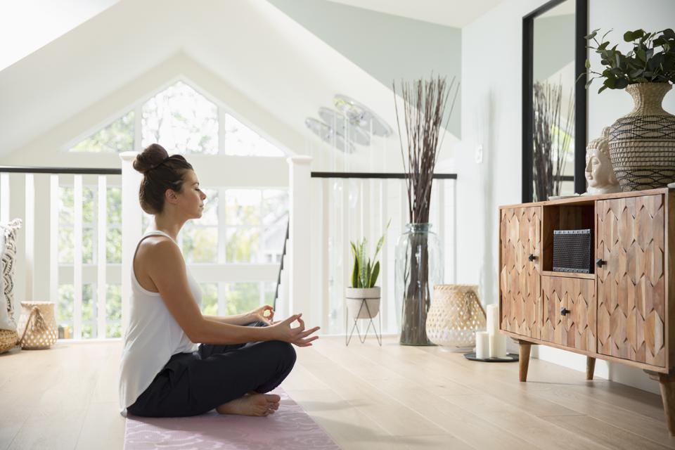 Serene woman meditating at home