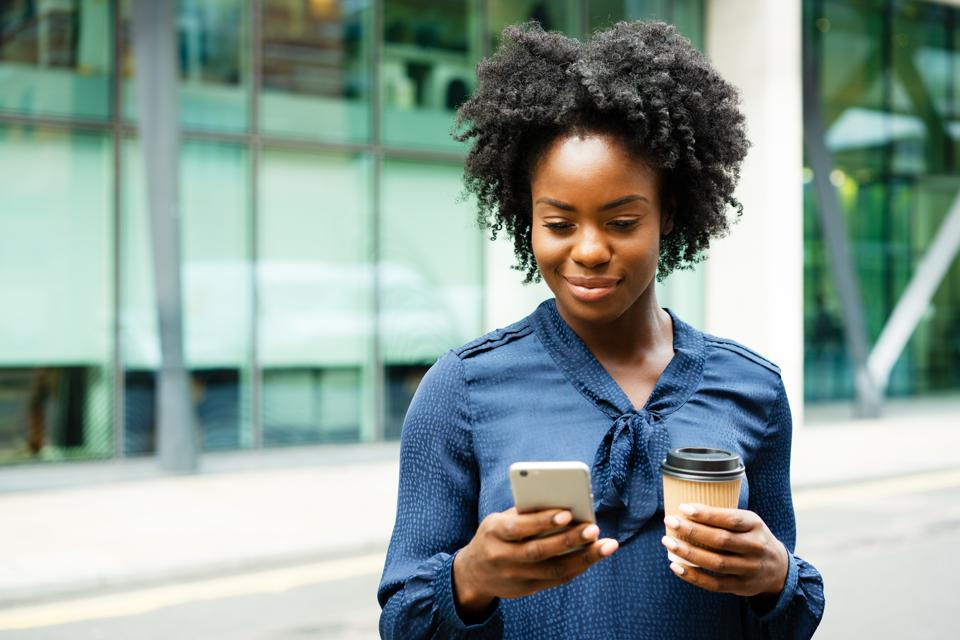 Woman using smart phone, holding coffee
