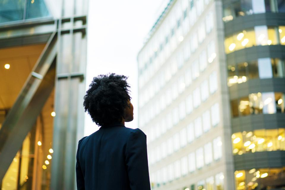 Woman looking up at office buildings