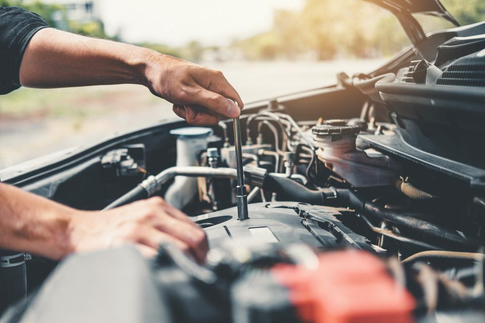 Auto mechanic working in garage Technician Hands of car mechanic working in auto repair Service and Maintenance car check.