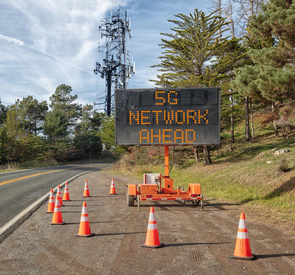 5G communications tower for mobile phone: Roadside warning sign on rural road.