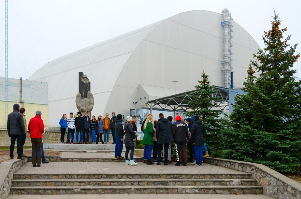 Group of tourists at monument to liquidators of accident at Chernobyl NPP on background of object ″Shelter″ over 4th power unit in Exclusion Zone