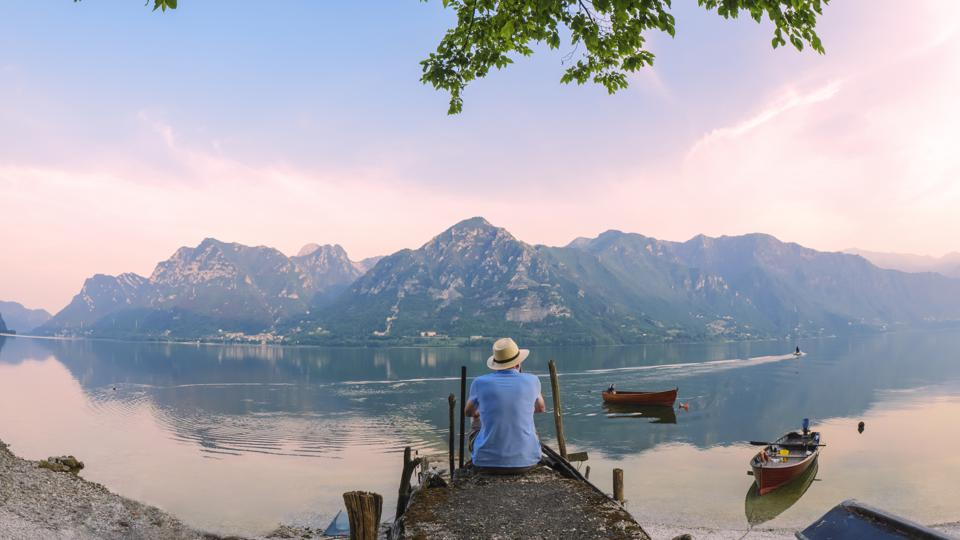 Italy, Lombardy, back view of man sitting on jetty at Lake Idro at morning twilight