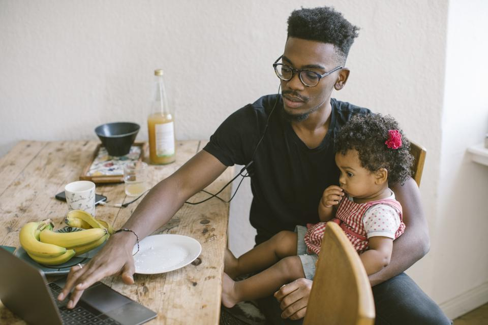 Young man using laptop while sitting with daughter at dining table in house