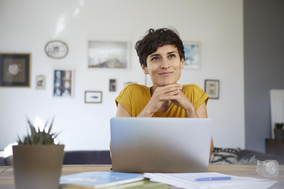 Portrait of smiling woman at home sitting at table using laptop