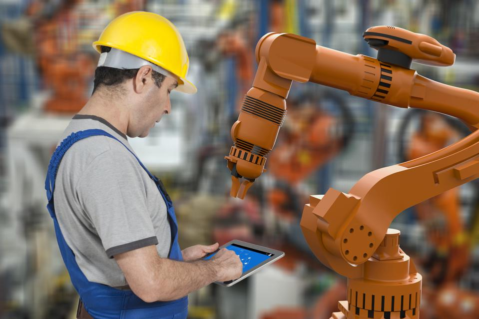 Factory worker using digital tablet to operate Robotic Arm