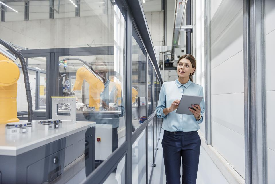 Businesswoman checking robots with digital tablet in high tech company