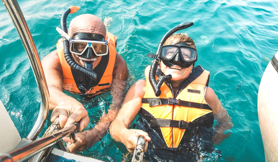 Retired couple taking happy selfie in tropical sea excursion with life vests and snorkel masks - Boat trip snorkeling in exotic scenarios on active elderly and senior travel concept around world