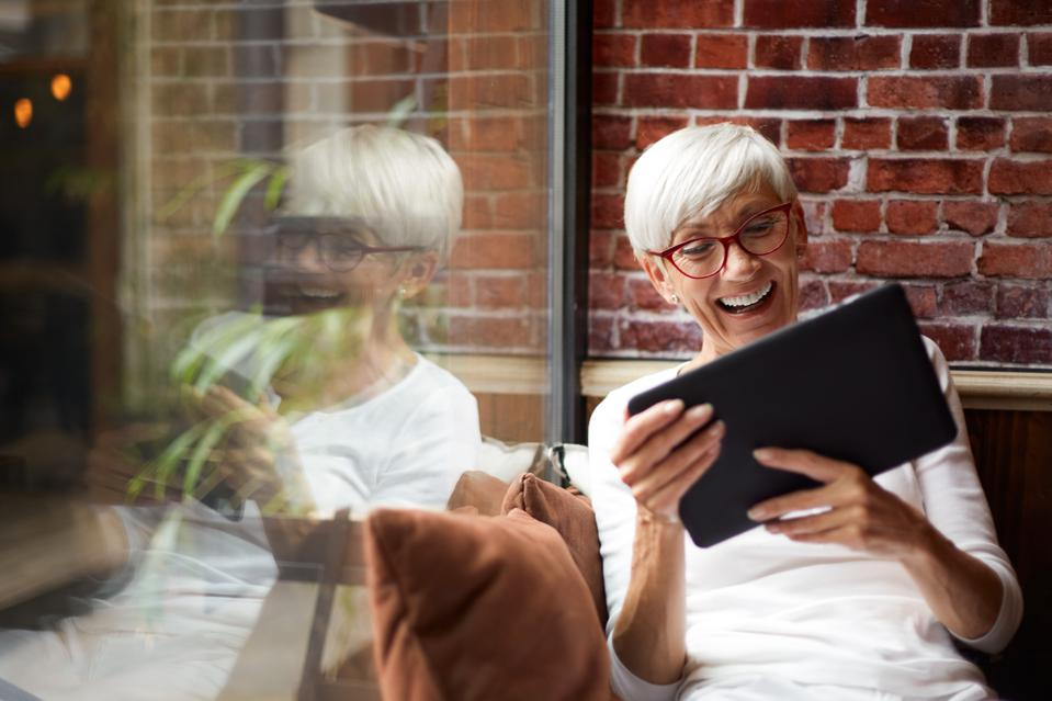 Elderly woman using a digital tablet and having a good time while sitting comfortably next to a glass window