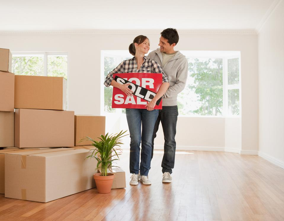 Couple holding sold sign for their new house