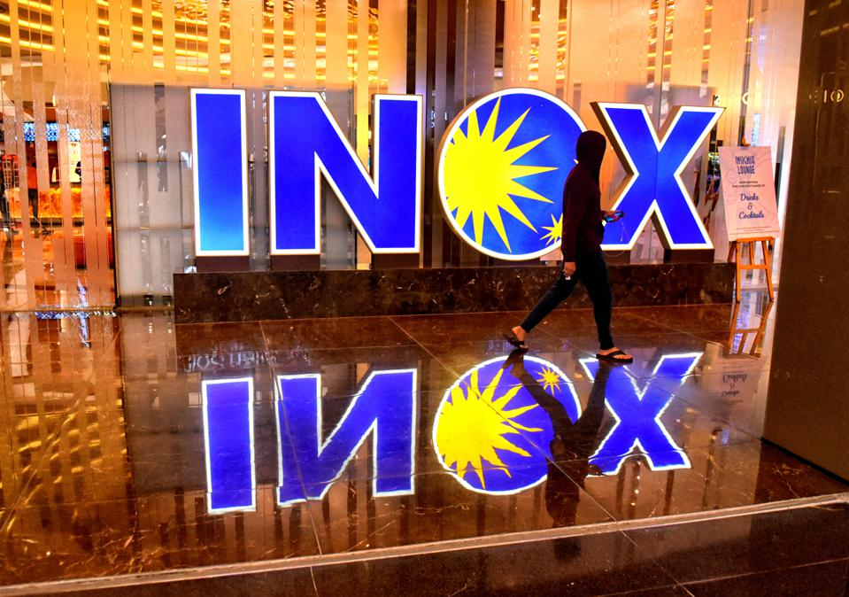 A visitor seen walking passed an Inox cinema hall  logo at...