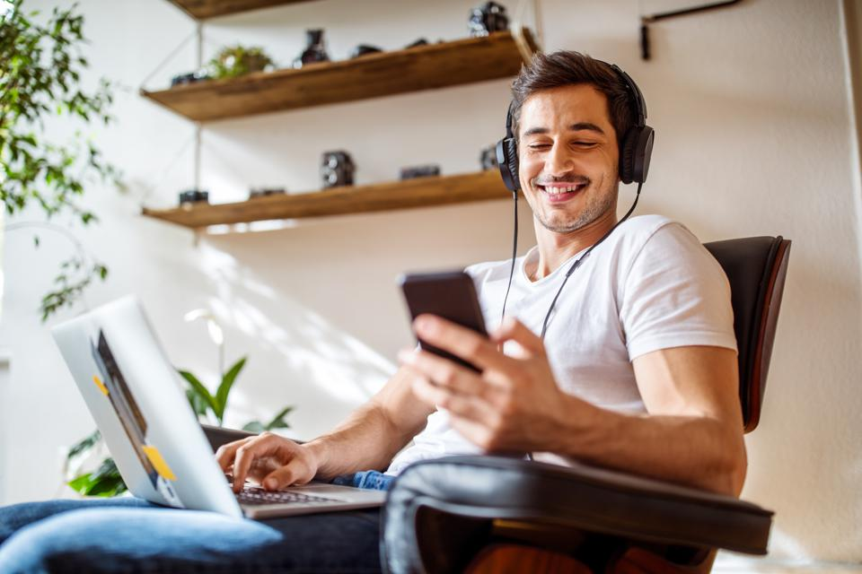 Someone smiling while listening to content on his smartphone.