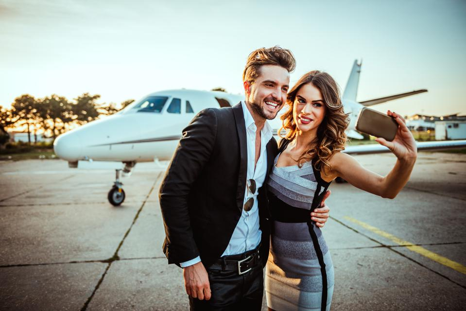 Rich and famous couple taking a selfie for social media while embracing each other in front of a private airplane parked on a tarmac