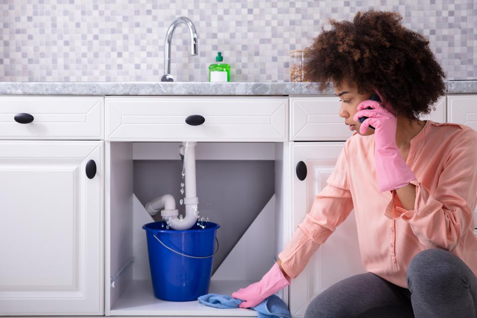 Woman Calling Plumber In Front Of Leaking From Sink Pipe