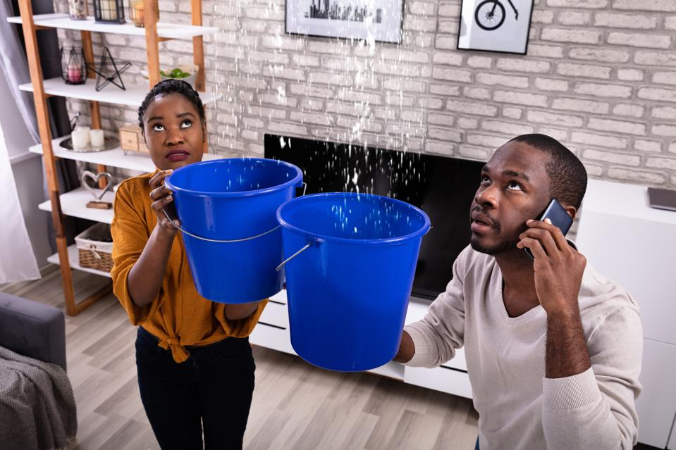 Couple Using Bucket For Collecting Water Leakage From Ceiling