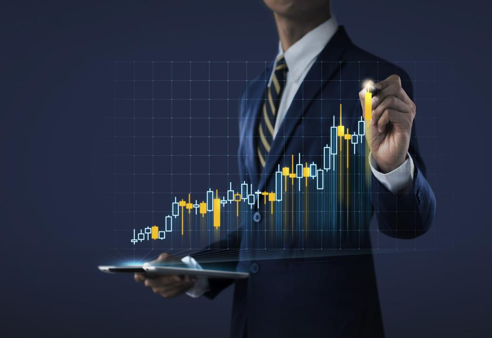 Business growth, progress or success concept. Businessman is drawing a growing stock bar on dark tone background.