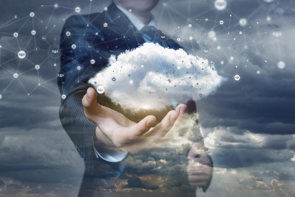 A networking cloud is hanging above the hand of a businessman.