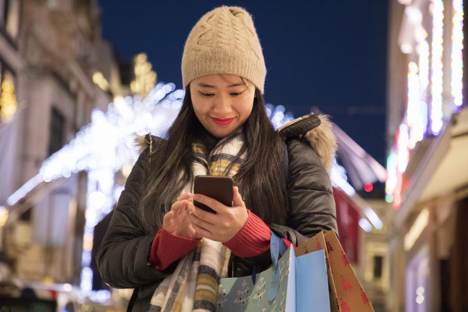Asain woman checks mobile phone during christmas shopping.