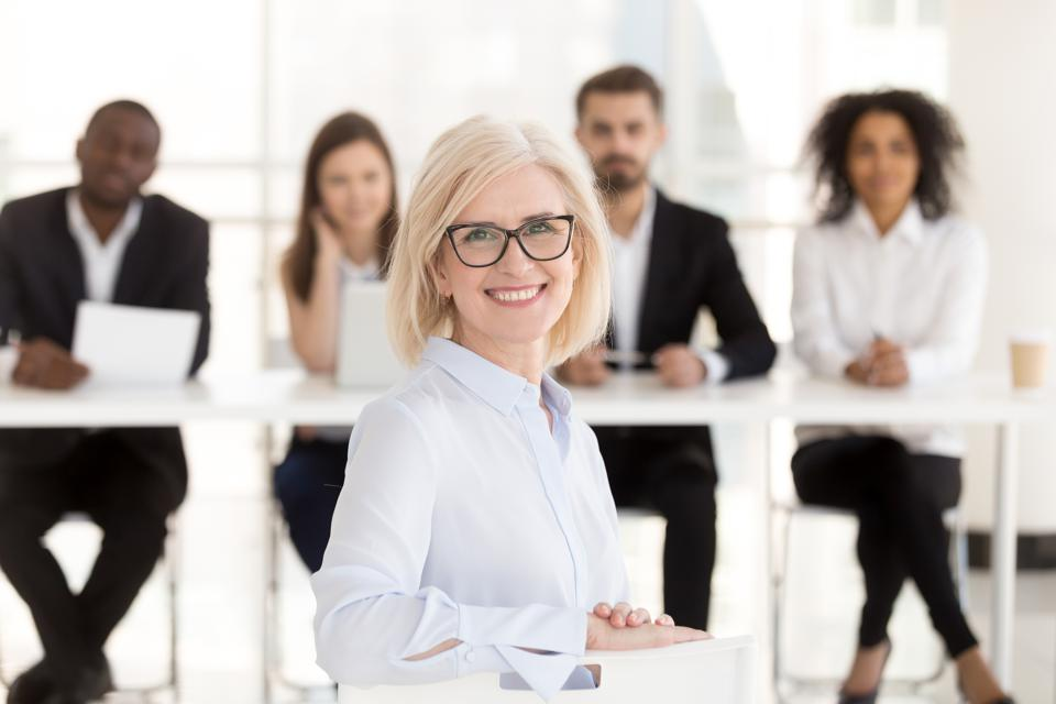 Smiling senior woman job applicant looking at camera during interview