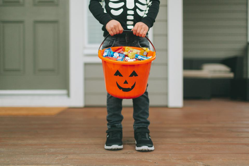 Low Section Of Boy With Sweet Food In Bucket Standing At Home During Halloween