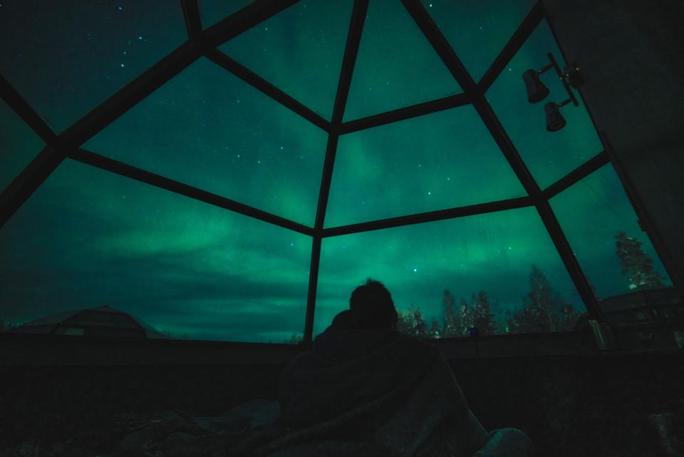 A couple enjoy view of Aurora Borealis and stars in glass igloo in Rovaniemi, Finland