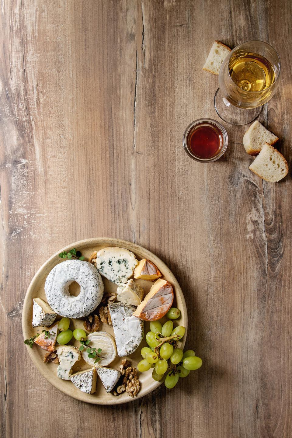 Cheese plate assortment of french cheese served with honey, walnuts, bread and grapes on ceramic plate with glass of white wine over wood texture background Top view, space