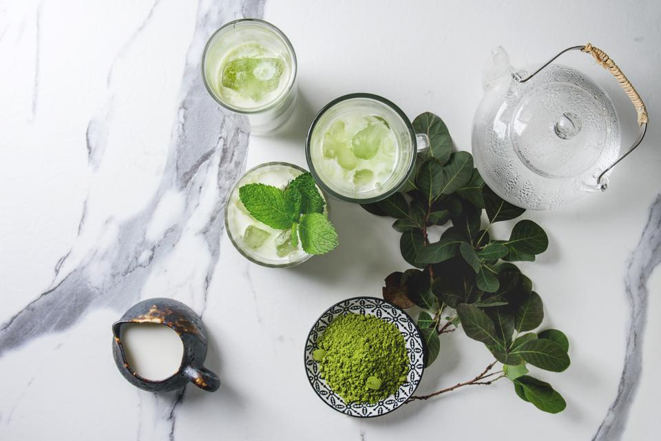 Matcha green tea iced latte or cocktail in three different glasses with ice cubes, matcha powder and jug of milk on white marble table, decorated by green branches Grey wall at background