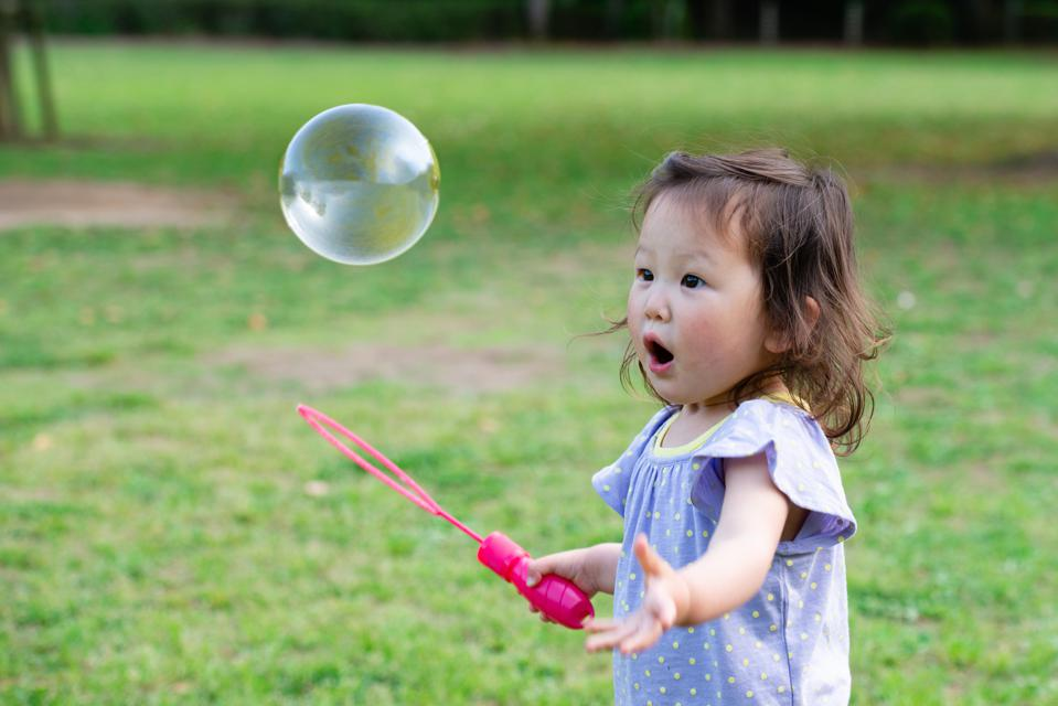 Toddler girl playing with soap bubbles