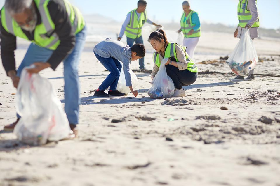 Mother and son volunteers cleaning up litter on sunny, sandy beach