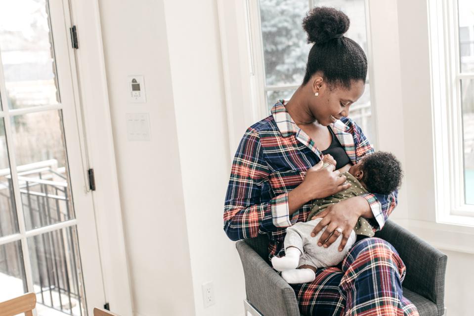 Mom and newborn baby breastfeeding moment