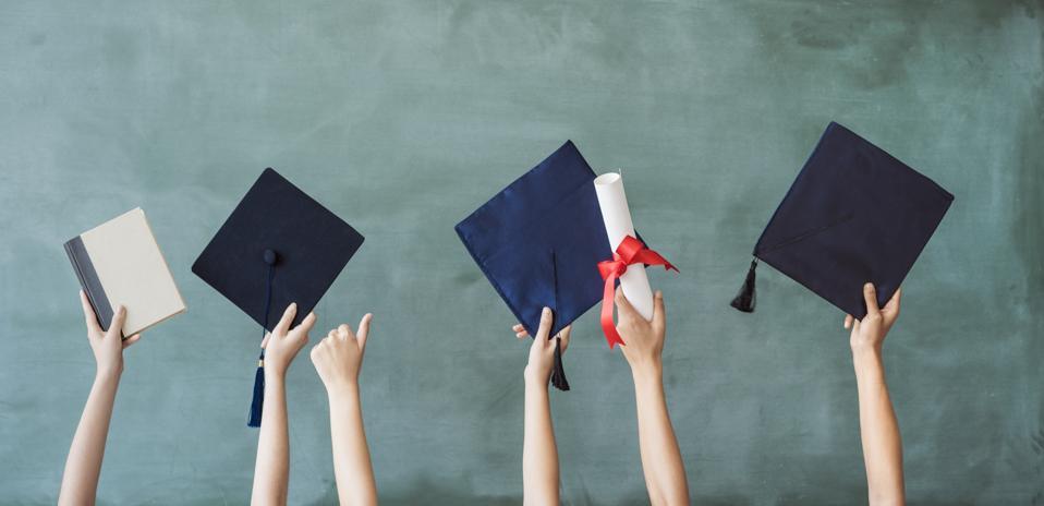 Raising hands with graduation cap on chalk board