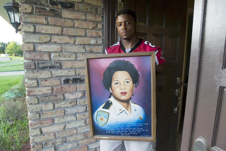 Warrick Dunn holding a portrait of his mother in his home town.