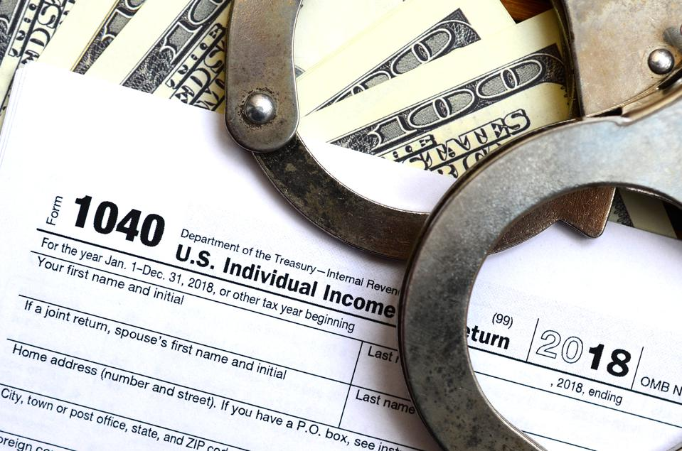 Police handcuffs lie on the tax form 1040. The concept of proble