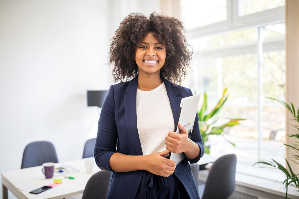 Portrait of confident african businesswoman with laptop