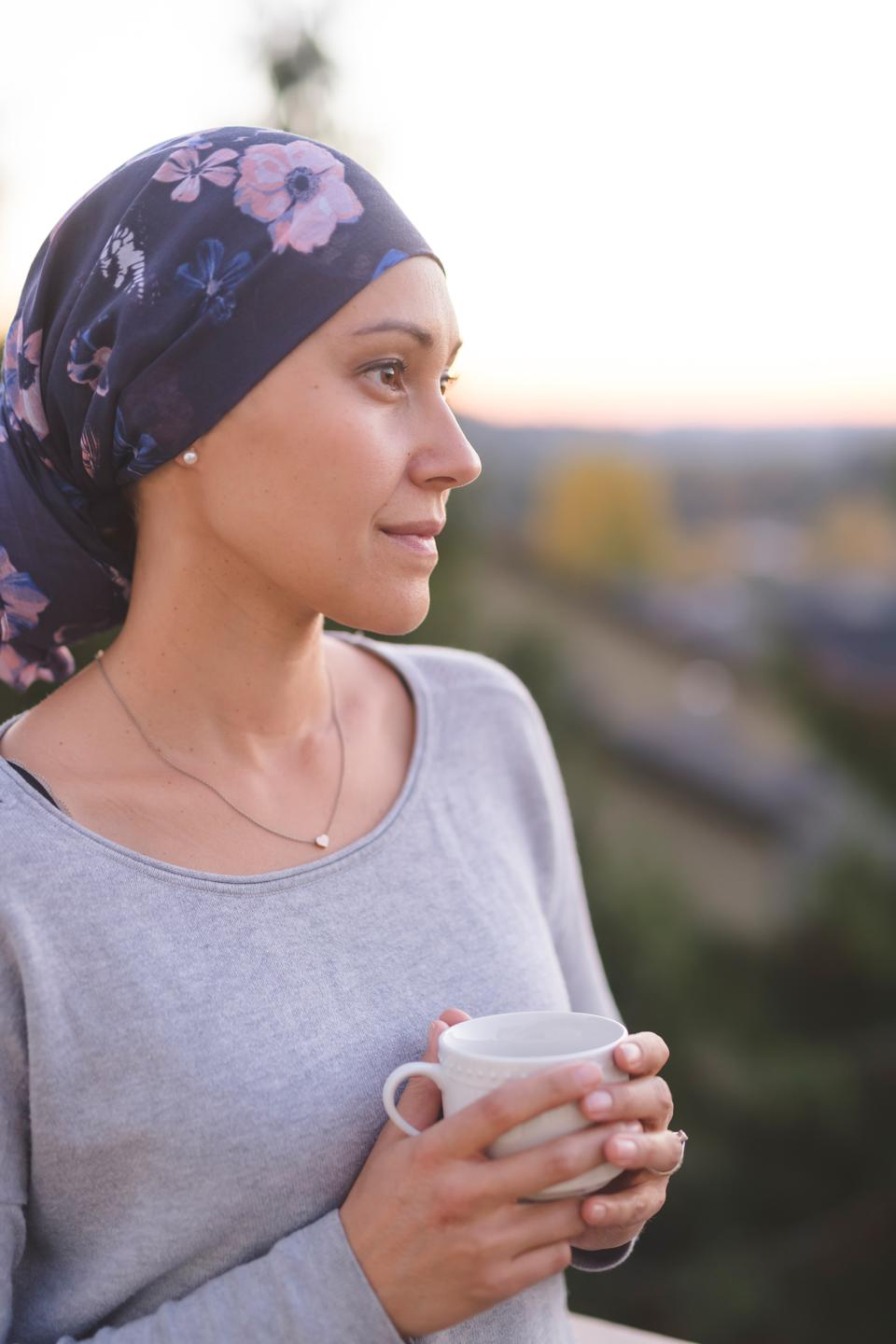 Ethnic woman battling cancer standing outside and looking off-screen with a contemplative expression