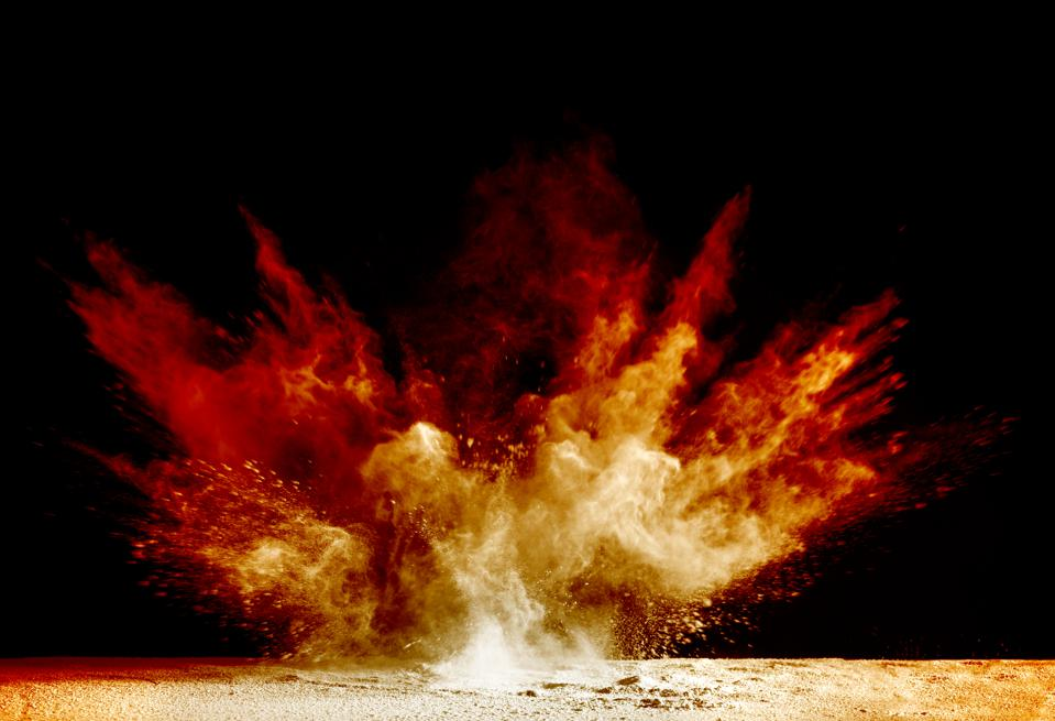 Explosion by an impact of a cloud of particles of powder of color red and yellow on a black background.