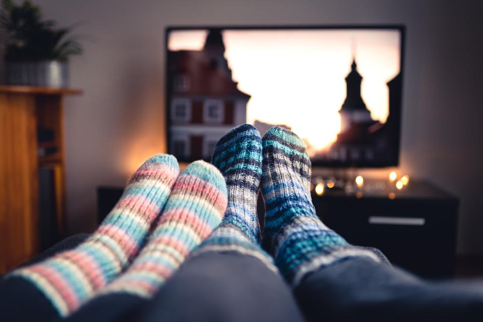 Woman and man sitting or lying together on sofa couch in home living room using online streaming service.