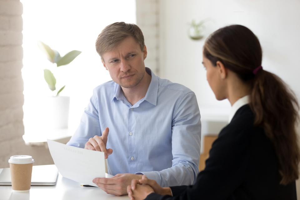 Doubting hr manager looking with suspicion at applicant