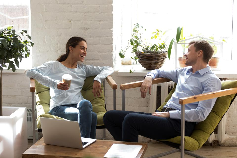 Happy woman laughing with colleague, drinking coffee during break