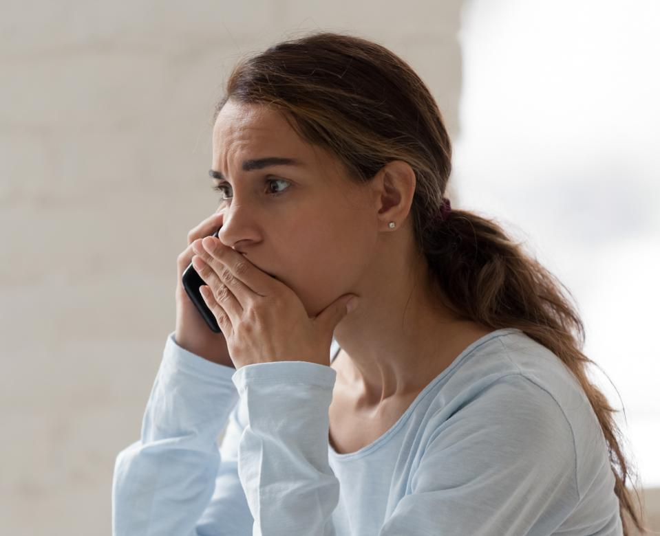 Scared shocked woman talking on phone, receiving bad news