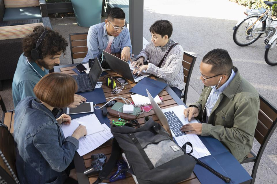 Millennial entrepreneurs working at cafe table