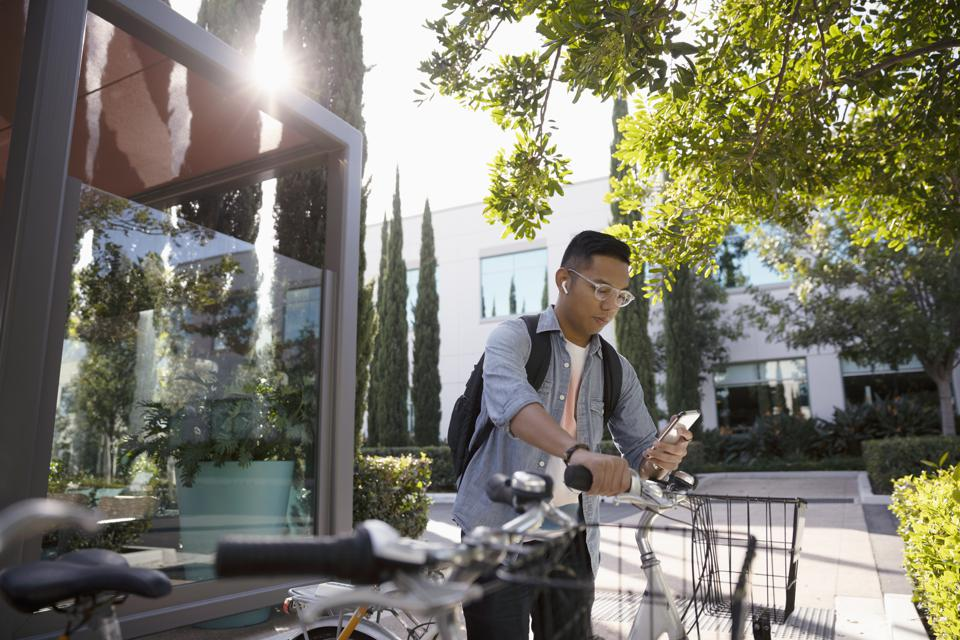 Young man with bicycle using smart phone on sidewalk