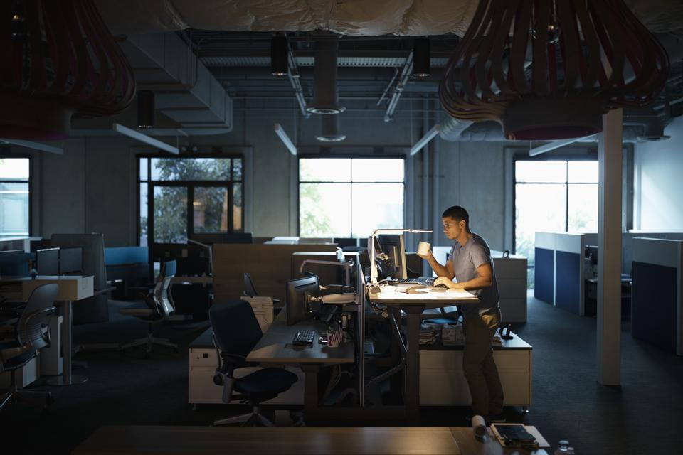 Dedicated businessman working late at computer, drinking coffee at sit-stand desk in dark office