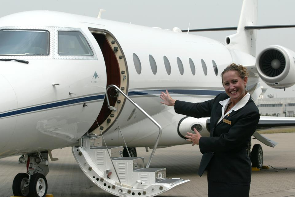 Private jet travel for business and pleasure - Stewardess Cherie Drummond in front of a Gulfstream jet at Chek Lap Kok.  04 March 20