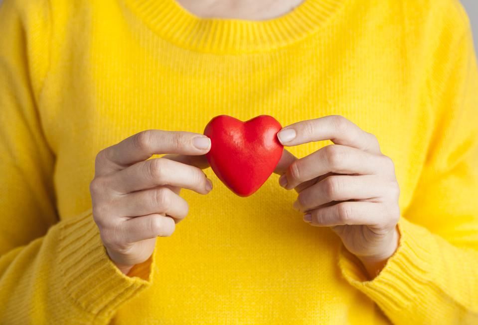 Young woman holding red heart, health insurance, donation, love concept