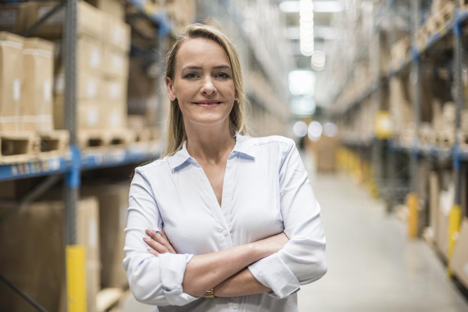 Portrait of smiling woman in factory storehouse