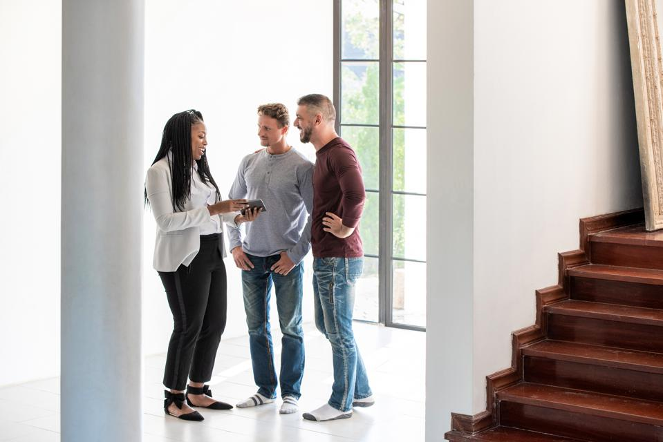 Male gay couple talking with real estate agent about new house