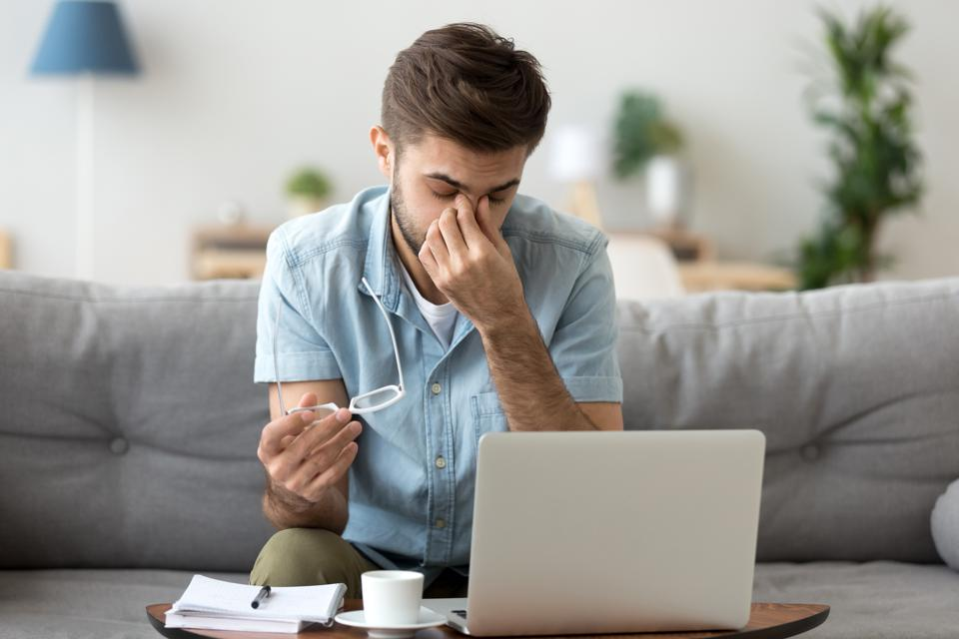 Tired young man feeling eye strain headache after computer work